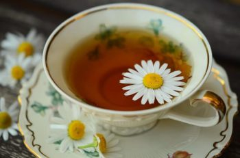 Porcelain tea cup filled with chamomile tea.
