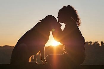 How To Grieve The Loss Of A Dog - Woman kissing her dog in the sunset.