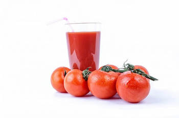Glass of tomato juice with a straw and 4 ripe tomatoes in front of glass.