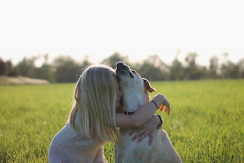 Personalized Dog Memorial Gifts - Blonde girl hugging a white dog outside in a field of grass.